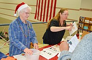 Shawnee Community Services founder Evelyn VanKemseke, left, and volunteer Susan Colston greet children and hand out drawing tickets during the organization's 29th annual Children's Christmas Party Saturday afternoon at the Shawnee Civic Centre. About 500 children and parents attended the free event.