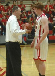 Dane Erickson is congratulated by coach Shawn Phillips after scoring his 1,000th point on senior night.