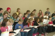 Members of Vivo Allegro, the ensemble for treble singers grades 4-7, make notes on their music during rehearsals on Monday.