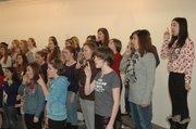 Members of Allegro Con Moto, the ensemble for girls grades six through 12, do vocal warm-ups at Monday&#39;s rehearsal.