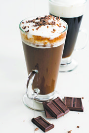 For traditional Irish coffee, gently pour softly whipped cream over the back of a spoon so it floats on top of the coffee — the hot coffee is meant to be sipped through the cream.