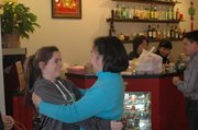 Catie Flipse, left, of Bonner Springs gives Maria Lui a hug while Flipse's father pays for their carry-out Monday at Red Fortune. Lui said she has known Flipse since Flipse was a small child.
