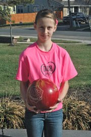 "Kyah holds her ""aggressive"" DV8 ball, one of seven bowling balls she owns, which she used to conduct her experiments for her prize-winning science project."