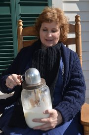 Sharon Uhler, curator of education at Shawnee Town 1929, churns butter last Friday on the front porch the living-history museum's farmhouse, part of the Shawnee Town 1929 Truck Farm that will be hosting a grand opening on May 4.
