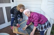 Testing their washboard skills, Abby Leardi, left, and Ellie Batliner, were among third-graders at Our Lady of the Presentation Catholic School in Lee's Summit, Mo., who toured the Shawnee Town 1929 Truck Farm during a field trip Friday.