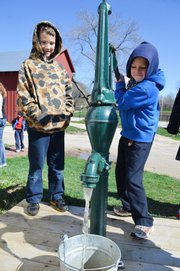Colin Schuster, right, pumps water from a cistern at the Shawnee Town 1929 Truck Farm as fellow third-grader Hunter Brennan looks on during a Friday morning field trip to the site by Our Lady of the Presentation Catholic School students in Lee's Summit, Mo.