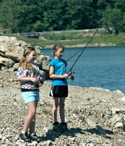 Emma Rawlings and Emma Morgan test the waters at last week's youth fishing clinic.