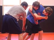 Colby Community College wrestling coach David Nordhues instructs J.T. Ellis, 15, and Holden Lentz, 12, during the final day of a wrestling camp at Bonner Springs High last week.