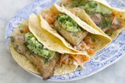 This recipe for fish tacos calls for lightly flouring and sauteeing fish instead of deep-frying it, then topping it with buttermilk avocado puree instead of a mayonnaise-based sauce.