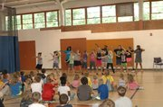 One of the camp groups performs a dance during the variety show Friday as other campers look on.