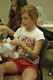 "Mercedes Pugh ties a string around the plastic bag ""jellyfish"" at Monday's Teenopolis event."