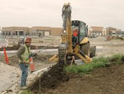 Key Construction Co. workers prep the parking lot of the new Walmart Supercenter in western Shawnee on Monday. The company announced it will hire 200 workers, most of them in August, to prep the store for its fall opening.