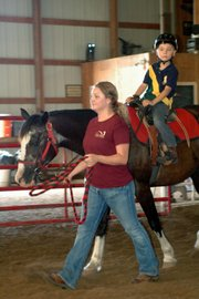 Charley Olsen looks ahead as a Due West staff member leads his horse around the indoor arena during his lesson Tuesday.