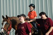 Bruce VanCleave of Bonner Springs smiles as a group of Due West staff lead his horse outside during his lesson Tuesday.