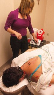 In Patricia Fraker's case, to shorten the acupuncture therapy time, Dr. Kimberly Flaming connects the needles with colorful wires that deliver low-level electrical current into points on Fraker's body.