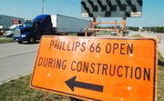An orange sign marks the entrance to the Phillips 66 gas station, obscured by tractor-trailers and construction equipment, on the south side of Shawnee Mission Parkway.