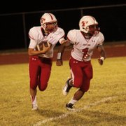 Tyler Ford, left, looks for running room behind Cole Holloway.