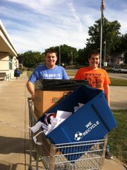 "Cody Crider (left) and Steven Shonkwiler take recycling out to the recycle dumpster at Bonner Springs Elementary School. The two Bonner Springs High School special education students take part in a new program that allows them to go out and ""work"" in the community."