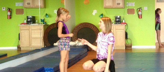 Kristin Mance, 19, talks with Audrey McCarty, 6, before a tumbling class on Monday. Mance is the owner of Judy's Studio of Tumbling and Dance II, 15630 Pinehurst Drive, in Basehor.