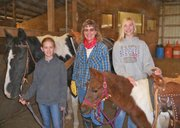 Freedom Farm volunteers (from left) Anna Owsley, Luanne Engelmann and Harper Kelly pose with Freedom Farm ministry horse Gibbs and pony Lollipop.