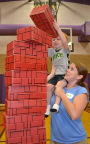 Janell Barker helps her son, Jack, add one more brick to his tower at BLOCKFest last year.