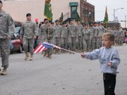 Mason Lake, 3, of Lansing waves his flag for soldiers at the Leavenworth Veteran's Day Parade Monday morning.