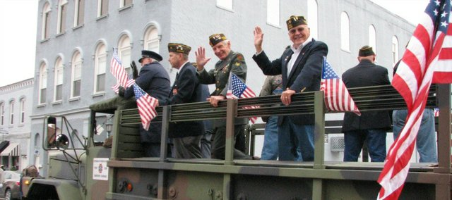 Members of the Basehor VFW Post 11499 wave to spectators at the Leavenworth Veteran's Day Parade on Monday.