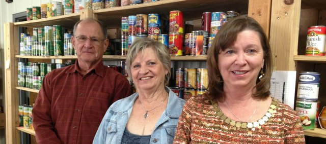 Glenda Briscoe (right) with Jackie Lee, a volunteer from the Basehor United Methodist Church, and Jeff Bohndorf, a member of the BLAS board, stand in front of the shelves on nonperishables.