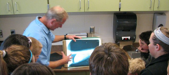 John Teeter, a veterinarian at Nall Hills Animal Hospital in Overland Park, shows students at Basehor-Linwood Middle School X-Rays of various animals who had swallowed things they shouldn't have.