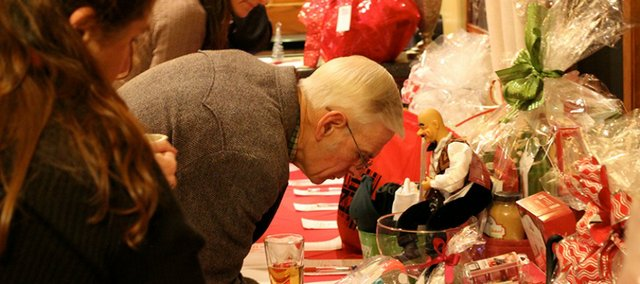 Roger Brandt, a Basehor Chamber of Commerce board member, bids at the silent auction during the Christmas Celebration on Dec. 5.