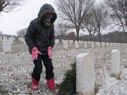 Vanessa Thurston, 9, of Basehor places a wreath on a headstone at Leavenworth National Cemetery.