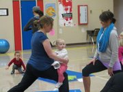 Kaitlyn King holds her one-year-old daughter Wynni as she maintains a yoga pose at the Family Fun Fitness class.
