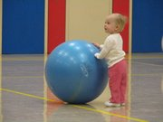 Wynni King, 1, looks toward her mother Kaitlyn King while playing with an exercise ball during an exercise at the Family Fun Fitness class.