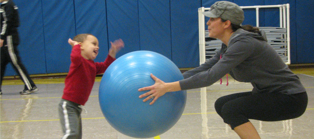Heather Sambol holds an exercise ball in front of her during a squatting exercise as her two-year-old son Weston bangs on the ball for fun.
