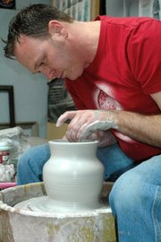 Trent Freeman, Edwardsville ceramics artist, throws a vase on the potter's wheel Feb. 26 in his home studio.