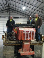 (From left) Matt Dubois, Augie Pierce and Austin fisher stand on one the snow plow trucks used this winter. The dispenser on the back of the truck is capable of spreading salt and sand in a spray of up to eight feet.
