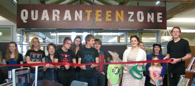 Spencer Brown (far right) stands with other youth as the ribbon is cut by teen services librarian Amy Schaffer Tuesday afternoon to officially celebrate the opening of the QuaranTEEN Zone.