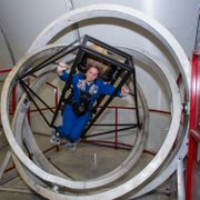 Monica Maurer uses the Multi-Axis Trainer, which simulates the disorientation one would feel in a tumble spin during reentry into the earth's atmosphere.
