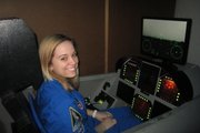 A Tonganoxie High School sophomore, Monica Maurer sits in an aviation challenge simulator.