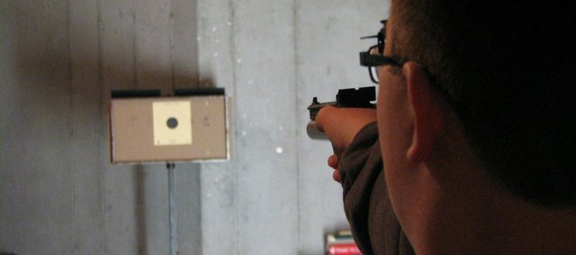 Blake Tucker takes aim at a target at his shooting range in his house. Tucker will compete in the state shooting competition on Apr. 12 following Junior Olympics.