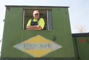Midland Railway volunteer Mike Beem leans out the window of a locomotive Saturday before the trained departed again for a Easter egg hunt at Norwood Station.