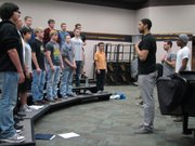 Dele Opeifa and members of re:Voiced demonstrate a breathing exercise for members of the BLHS choir class.