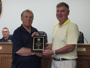 John Matthews receives a plaque from Mayor David Breuer commemorating his 21 years of service at Tuesday's City Planning Commission meeting.