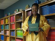 Joyce Skinner stand in her graduation gown and holds a diploma as she prepares to celebrate earning her high school diploma from Basehor-Linwood Virtual School.