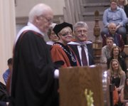 Baker University Board of Trustees Chairman Rich Howell lists President Pat Long's accomplishments after she and her husband, Dennis Long, were conferred honorary doctorate degrees Sunday at the university's Class of 2014 commencement.