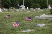 A cluster of U.S. flags fly in the wind Friday in Hubbel Hill Cemetery.
