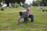 Tonganoxie American Legion's Don Harden tends to a grave marker after placing an American flag near it. The local Legion placed flags at gravestones in Tonganoxie cemeteries to honor those who served in military.