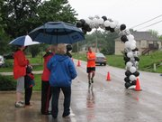 Spectators came out with umbrellas and rain gear to cheer on runners as they finished the Crazy Cow 5k run.