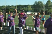 Survivors Peggy DeFries-Scholl, Janet Busch and Jody Shelton-Langly (from left) raise their arms triumphantly as they begin the opening Survivor's Lap for the 12th Annual Kaw Valley Relay For Life in 2014.