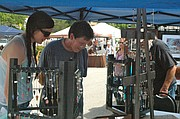 Erin and Nancy Carpenter of Bonner Springs check out items at the Sacred Stones booth Saturday at the Festival of the Arts.